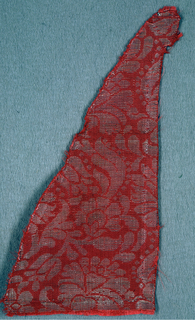 Design of flowers and leaves in silver on a red ground.