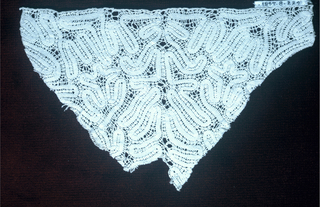 Fragment of continuous tape bobbin-made lace.