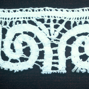 Lace border fragment with a symmetrical design of scrolls.