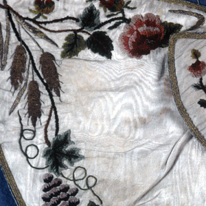 "Small cape for an ecclesiatic figure, the ""Bambino"". White silk moire embroidered with silk chenille in greens, purples, rose, and gold sequins and gold and silver thread. Design of grapevine, rose and grain aroudn border. Lined with blue silk with white brocaded floral design."