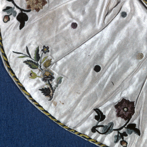 "Small cape for an ecclesiatic figure, the ""Bambino"". White satin embroidered with silk chenille and silk thread. All-over design of polychrome chenille dots with border design of a single flowering branch alternating chenille and silk. Lined with red taffeta."