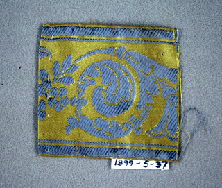 Ornate scroll, In blue on yellow.