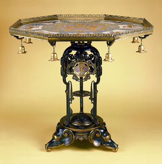Table with Chinese cloisonné enamel top set into an octagonal gilt-metal from which eight bells hang; the bronze base in Chinese style, highlighted with gilding with elephant head feet.