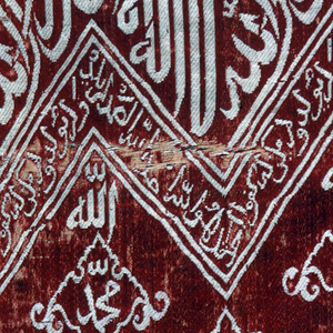 Fragment of woven silk with zigzag bands of Kufic script in white on a red ground. The inscriptions are translated as (top to bottom):   There is no god but Allah, Muhammad is the prophjet of God (repeated)  Say: He is God alone: God the Eternal! He begetteth not and is not begotten; and there is none like unto him  Allah (repeated) Muhammad (repeated)  Truly we have given thee an abundance; Pray therefore to the Lord, and slay the victims. Verily whoso hateth thee shall be childless