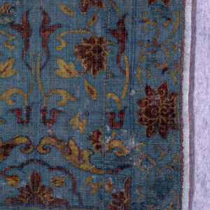 Yellow and brown floral and scroll motifs on blue background. Selvage at both side but piece is seamed in the center.