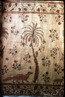 """The wide border, contained between two narrow guard borders with pattern of delicate flowering vine, exhibits a design of five types of palm trees – the Palmyra palm, banana, coconut, betel, and date palms – growing in a row, and forming a repeat pattern. On the ground appear a mongoose, a lamb, and shaggy gray dog wearing a collar. Several of the trees variously inhabited: the coconut palm is being ascended by the """"toddy"""" man, equipped with ladder, sack and other tools, to gather the fluid which will make the """"toddy"""" wine. A parakeet with red body and green tail clings to the trunk of a banana palm; a cobra is coiled round the trunk of the date palm, reaching toward birds which flutter about their nest; brown squirrels are busy on the trunk of the betel palm. The palm trunks are in red, or brown, or blue with red and blue foliage. Colors are two reds, two greens, blue, yellow, violet, and brown. Cotton is very fine, now a biscuit color, and glazed."""