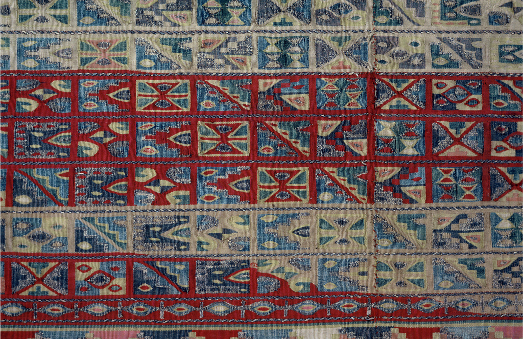 Mantle decorated with series of broad and narrow horizontal bands in reds, pale tan, cream, pale yellow, blues, silver.  A broad band across the middle is made up of ten narrow bands, with adjacent rectangles containing Inca geometric patterns and some adapted Tiahuanaco eye forms, separated throughout and edged top and bottom with variety of guard stripes.  Above and below this broad central band are slightly narrower pink bands, edged top and bottom with small stepped scallops and filled with close-set mermaids and bird, fish, animal and floral motives, seemingly scattered, but actually set symmetrically on either side of two central vases set one above the other in each band and filled with flowers and fruit. Two narrow bands with attendant varied guard stripes border the mantle at top and bottom; the inner red band is similar to the bands in the center of the mantle; the outer cream-grounded band contains a series of bird, fish, and floral motives symmetrically spaced on either side of the central axis of the mantle; pink guard stripes terminate the mantle at top and bottom.