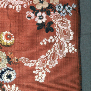 Fragment of silk brocade with sprays of flowers in blues, greens, yellows and soft reds, with white, lace-like scrolls on a coral ground. In the Rococo style.