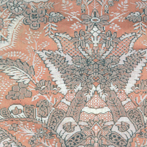 Silk fragment showing complex symmetrical pattern with florals in salmon, green and white. Backed with blue linen.