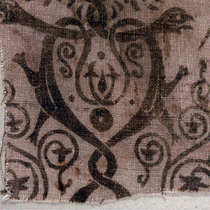 Fragment of printed linen with twining lizard-like shapes and scrolls, in gold on a rose ground.
