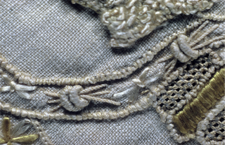 Off-white linen band embroidered in off-white, yellow and beige silks, with needle lace edging on three sides. A design of addorsed centaurs with spears and sheilds shooting arrows at dragons standing on scrolling vines, is repeated along the length of the band.
