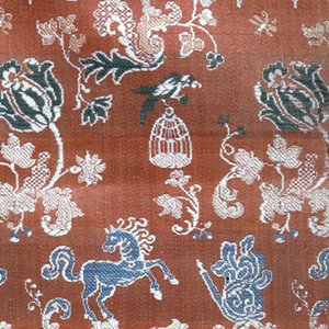 Bands of pattern – flowers, people, birds horses – on a pale red-orange ground. One green and white striped selvage.