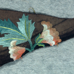 Fragment of dark brown silk grosgrain with bit of embroidery on one side. Part of large orange and yellow blossoms and green leaves. Triangular shape.