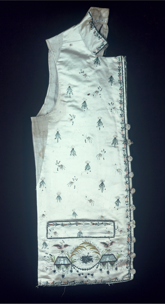 Men's waistcoat with standing collar, welt pockets and strait-hem. Off-white silk satin embroidered with scattered sprays all over and classical ornament along the lower edge. In soft greens and pinks with gold metallic.