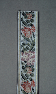 Multi-colored design of tulips and other flowers arranged on a curving stem on a gray ground with a white border.
