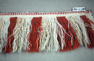 Fringe in red, cream and tan with a patterned heading and skirt threads arranged to form colored stripes.