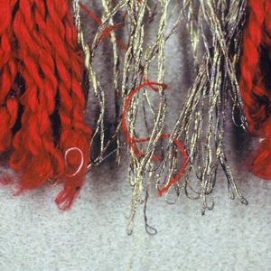Fringe in red and gold with a plain-woven heading. Skirt has red and gold threads, looped and twisted, that are arranged in groups.