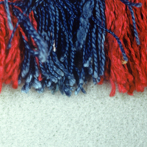 Fringe with a red and blue checkerboard heading. Red and blue skirt threads arranged to form stripes.