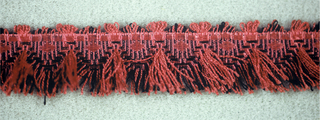 Fringe in red and black with a heading of lozenges and stripes and a picot edge at the top. Skirt threads hang from the middle and edge of the heading.