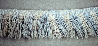 Fringe in blue and white with a plain-woven heading. Blue and white skirt threads are arranged in stripes.