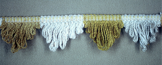 Fringe in gold, yellow and white with a plain-woven heading. Skirt threads, looped to form gold, yellow and white stripes, are scalloped.