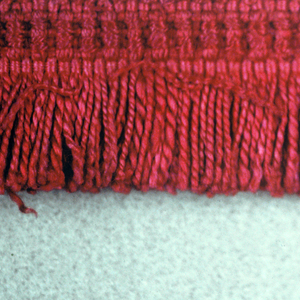 Red fringe with a woven heading and red skirt threads.