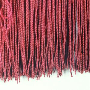 Red fringe with a heading woven in chain design. Skirt threads are looped and twisted.