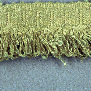 Yellow fringe with a woven heading in a chain design. Skirt threads are looped.