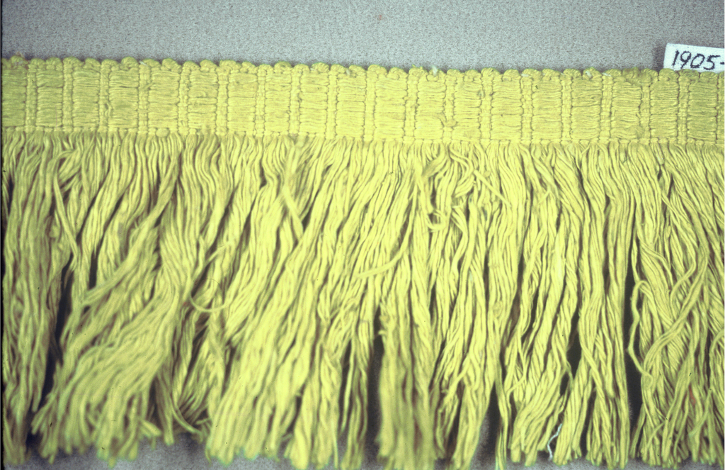 Yellow fringe with a plain weave heading and skirt threads.