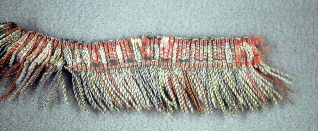 Pink, gray, yellow and white fringe with a woven heading and skirt thread arranged to form stripes.