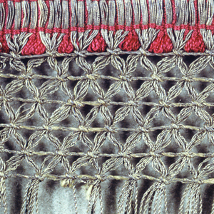 Red and metallic gold fringe with a red woven heading and narrow looped fringe overlaid with gold threads forming fringe. Band of trellis pattern at the top of the skirt using gold threads, twisted and looped.
