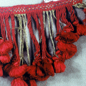 Fringe of red and gold threads with a patterned heading. Scalloped skirt threads in an alternating group of gold and red threads, each suppporting a red tuft.