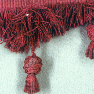 Fringe of red and gold threads with a heading and skirt threads cut into points; tufts hanging on red loops between points and at center of each.