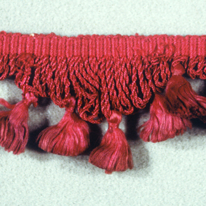 Fringe of red and gold threads with a heading and looped skirt threads arranged to give a scalloped edge; ornamented at intervals with red tufts.