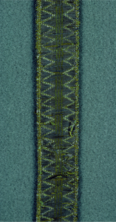 Design of plain center with saw tooth borders in yellow and metallic thread.