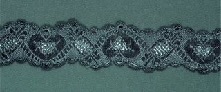 Design of stylized heart and leaf forms with scalloped borders forming serpentine bands. In white with silver thread and strips.
