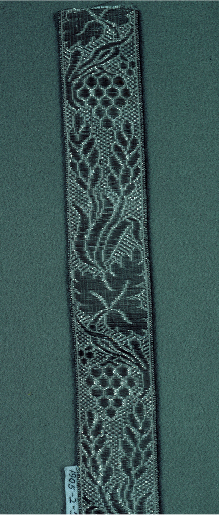 Design of vine leaves and grapes in white and metallic thread.