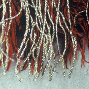 Fringe with a red heading and borders of gold thread. Overlay of gold threads on red skirt.