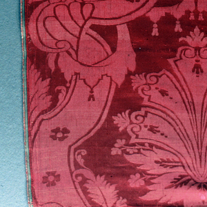 Long vertical length of red damask has symmetrical broad scrolling bands with acanthus foliage curling about them. Palmette between bands is at top. In center is a single large figure of Pope Gregory the Great (ca. 540–604), wearing the papal tiara, his right hand raised in benediction, and holding a crozier of a double cross in his left hand. A dove, an attribute of Gregory, hovers close to his right ear. The figure of the Pope is brocaded in white silk, and silver and gold metallic threads. Beneath the Pope is a large-scale floral design.