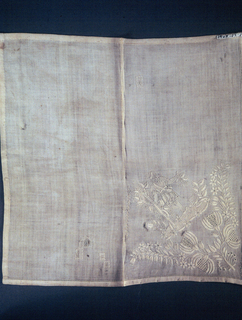 Embroidered ornament in one corner showing man picking fruit from a tree and two floral sprays. Hemstitching on two sides of handkerchief.