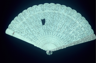 Ivory brisé fan carved and pierced to resemble lace with figures, boats, houses, trees. Guards carved in high relief.