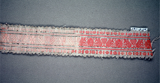 Pink and white trimming fragment of a floral ornament in red-orange silk arranged on a band between borders with gilt stripes and picot edges.