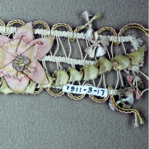 Multi-colored trimming woven in an open design with flowers made of colored ribbons and floss threads that are knotted and fringed.