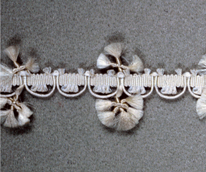 White trimming in a design of scallops with knotted and fringed ornaments.