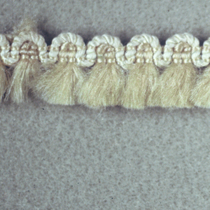 White skirt threads arranged in bunches with heading outlined in silk cord forming scallops at the top.