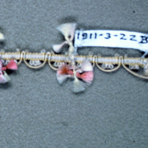 Woven heading with a cord forming scallops on one edge and ornaments of colored silks knotted and fringed on the other.