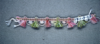 Woven heading with a cord carried through as scallops and tufts of pink and green silk placed between the scallops.