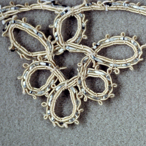 Trimming of gray and white silk cord and flat copper strips twisted into an ornamental design of loops.