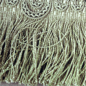 Green fringe with a woven pattern in the heading and heavy green threads overlaid to form scalloped edge. Skirt of green twisted threads.