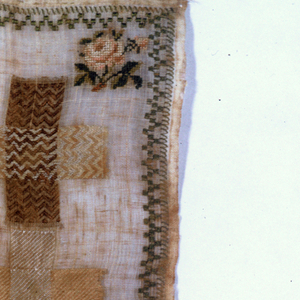 In the center, C.G.C.L.R 1821 and a floral wreath, surrounded by darning crosses in stitches useful in mending damask. Narrow border with floral sprays in the corners.